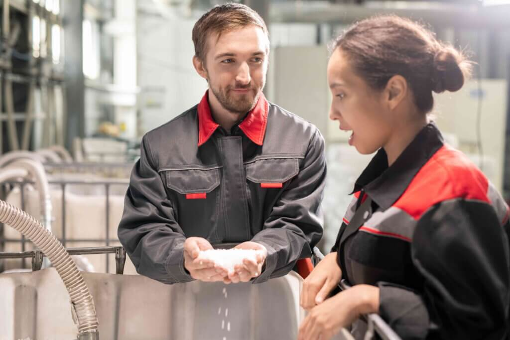 Two young quality control managers discussing characteristics of white plastic pellets while one of them holding pile over large container.