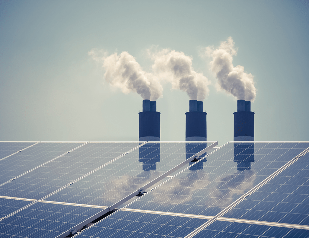 A photo of three chimneys blowing smoke against a blue sky, with solar panels in the foreground to symbolize a clean energy transition.
