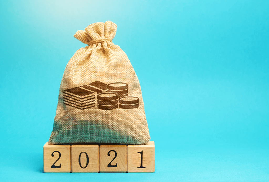 A burlap sack with bills and coins shown on the front sitting on four wooden blocks that say 2021.