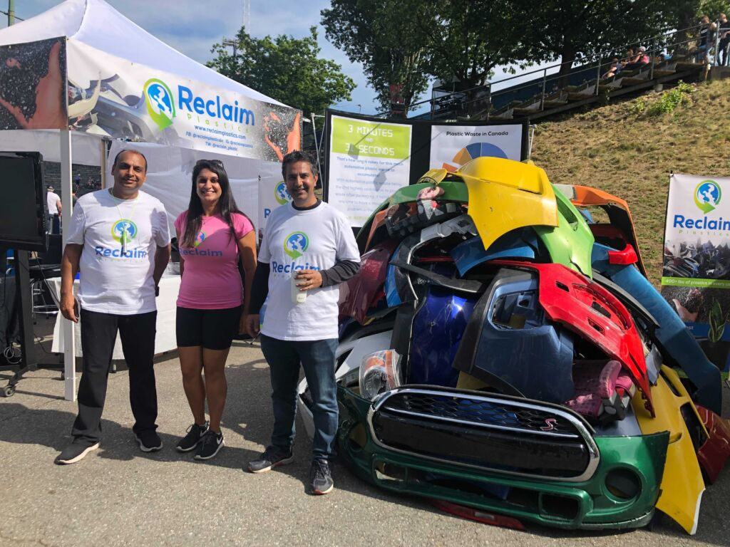 The photo shows three people standing between a pile of damaged car bumpers and the Reclaim Plastics booth outside at the PNE in Vancouver, BC.